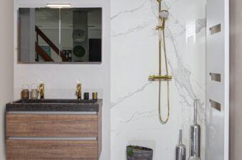 Opstelling met wastafel en gouden douche in badkamer showroom Broek op Langedijk